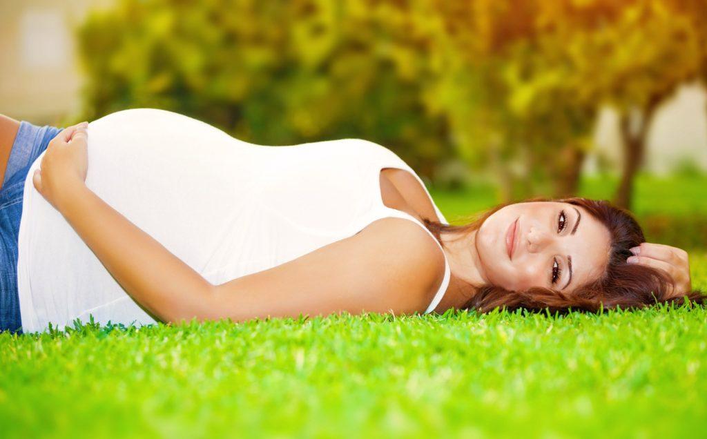 Happy pregnant woman lying down